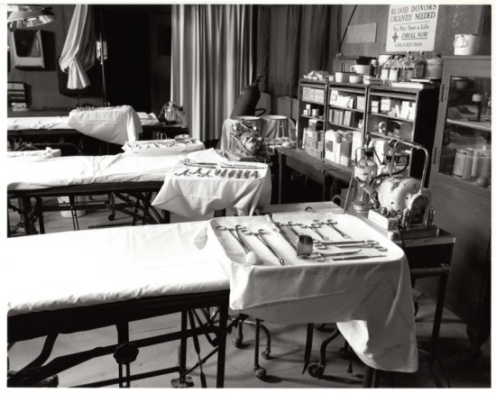 Black and white photograph of operating room set, with surgical tools laid out next to beds