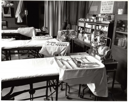 A black and white photograph of three cots with trays covered in surgery equipment. There is shelving with boxes and jars and white, floor-length curtains.