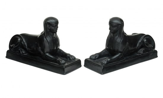 Two shiny, black statuettes. They have the bodies of lions but human heads with royal Egyptian-style head coverings.