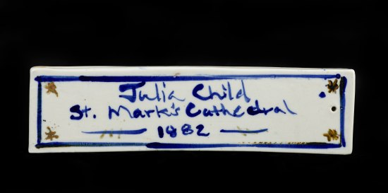 White rectangular weight with blue painted text.