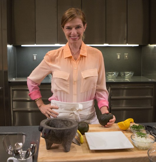 Woman faces camera and smiles. She is wearing a small microphone. Standing in a kitchen/stage. Avocado on counter top. Cabinets behind her.