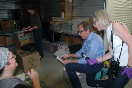 A photograph of several people inside a storage unit. A woman looks through papers in the back. Another woman sits in the foreground, her head and arm the only visible parts of her body. A man kneels with some sort of paper or notepad in his hand. He points to something as another woman beside him with purple gloves holds a microphone up. She wears a machine with a black strap on her side, which the mic connects to.
