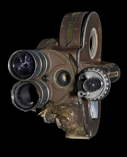 Photograph of a film camera. Viewfinder and film reel are visible. It appears to be worn and hard-used, perhaps slightly destroyed in some areas.