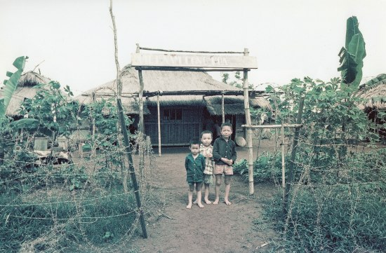 Three children (probably boys), who are barefoot, stand in front of a building with a hut-style thatched roof. The entry way in front of them is made of wood. A garden on both sides of the boys.