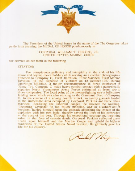 "Citation for Medal of Honor. Gold text, blue ribbon image. Text: ""...in a valiant act of heroism, hurled himself upon the grenade absorbing the impact of the explosion with his own body, thereby saving the lives of his comrades at the cost of his own. Through his exceptional courage and inspiring valor in the face of certain death, Corporal Perkins reflected great credit upon himself and the Marine Corps and upheld the highest traditions of the United States Naval Service. He gallantly gave his life for his country."""
