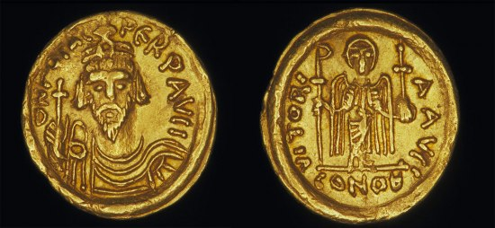 A gold coin with a bearded man on one side and an angel standing on the other