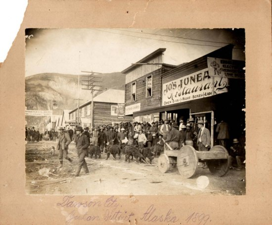A busy street scene with a large group posing for a photo in front of a restaurant. In the foreground, a group of dogs pull a wagon or converted dog sled with wheels