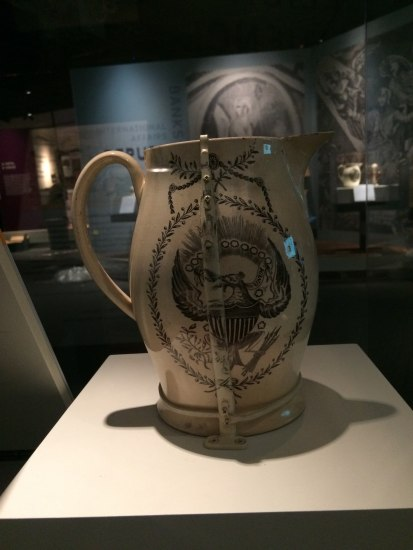 An ivory pitcher sits on a pedestal and is lit from above. It has an eagle with laurels painted brown on one side and some sort of rod-like object painted to match the pitcher runs up the side of it and encircles the base.