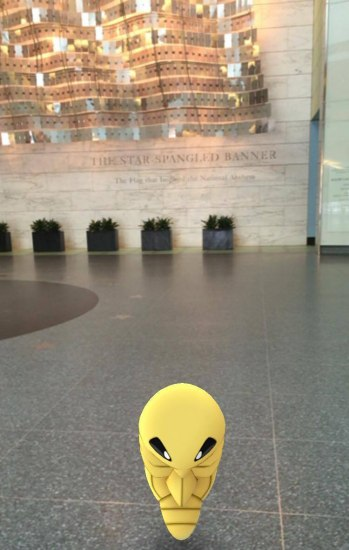 Screen shot from Pokemon game showing yellow cartoon Pokemon and museum lobby with abstract American flags