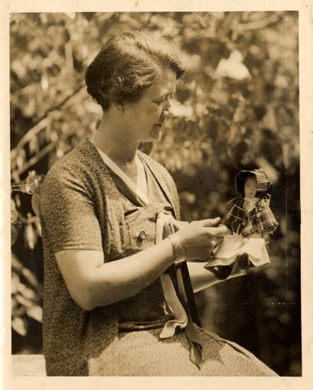 A photograph of Portia Sperry holding a Nancy Hanks rag doll, taken in 1934.