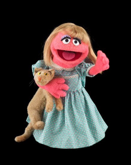 Puppet with pink skin, smiling mouth, happy eyes, blonde hair, and a blue dress. She hugs a stuffed toy.