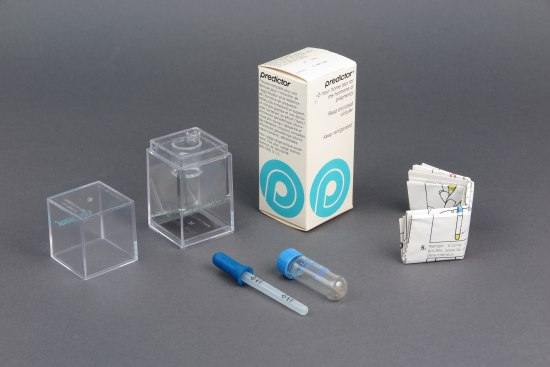"A rectangular box with the name ""Predictor"" at the top is surrounded by what it would have contained: instructions, a small pipette and vile, and a clear rectangular box (and accompanying lid) designed to hold the vile and pipette suspended over a mirror."