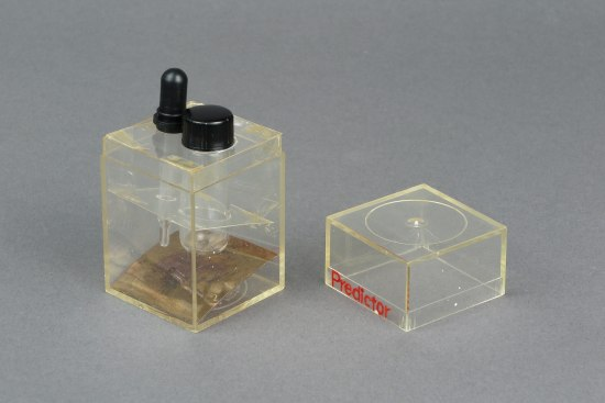 A clear box, holding a pipette and a small vile, over a tilted mirror.
