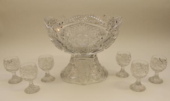 Glass punch bowl with a foot and six footed glasses
