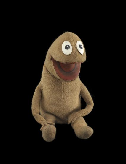 Small brown puppet with big white eyes, photo