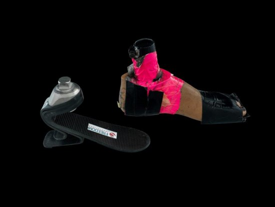 Two contraptions used as a prosthetic foot and socket for competition. The socket is black and looks like an upside down spring board with a metal piece protruding from the top. The prosthetic foot is tan in color and is wrapped with black and neon pink materials. There is a short pole extending from where an ankle would be.