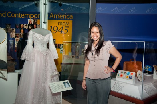 Natalia Flores poses beside her donated quinceañera gown in the museum's American Stories exhibition.