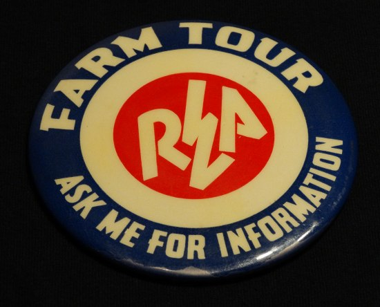 "Blue, circular pin with red ""REA"" logo in middle. The ""E"" is a lightning bolt. ""Farm Tour: Ask me for information"" it says."