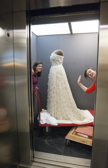 Two women iare in an elevator with a formal white gown that is on a low, flat wheeled cart. One holds a handle to the cart and one stands behind the door frame, waving with only her head sticking out.
