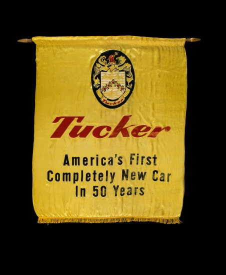 Photograph of a Tucker advertising banner. The yellow banner reads: 'Tucker - America's First Completely New Car in 50 Years""