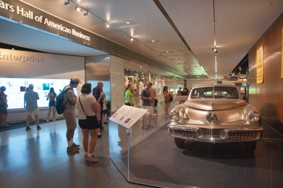 Photograph of museum visitors looking at the Tucker automobile's display on the museum floor.
