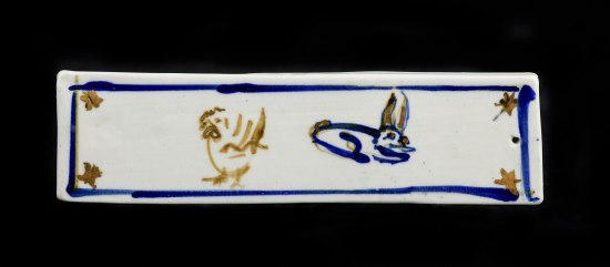 Rectangular weight in white. A little rabbit and chicken are painted on it in rustic style and a few leaves.