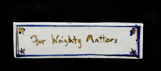 "Rectangular white weight with text painted on it in gold: ""For weighty matters."""
