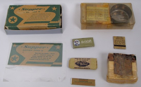"K-ration; original outer green color cardboard box contains: waxed cardboard box shell with ""CHESTERFIELD"" cigarette pack, toilet paper packet, one stick of gum, and eight biscuits, confectionery chocolate D bar, bouillon powder packet, can of pork loaf; manufactured by the Kellogg Company; World War II era."