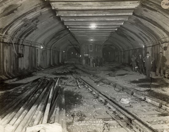 An empty subway tunnel. Unlaid train line sits to one side, workers stand to the other.