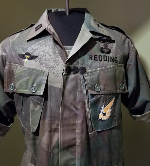 Green and brown military uniform. Owner's name, Redding, written on left breast