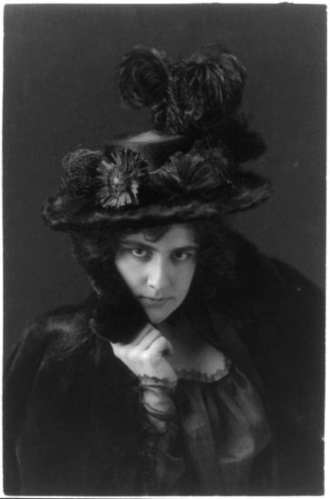Woman in fur coat and plumed hat looks into the camera in a model pose