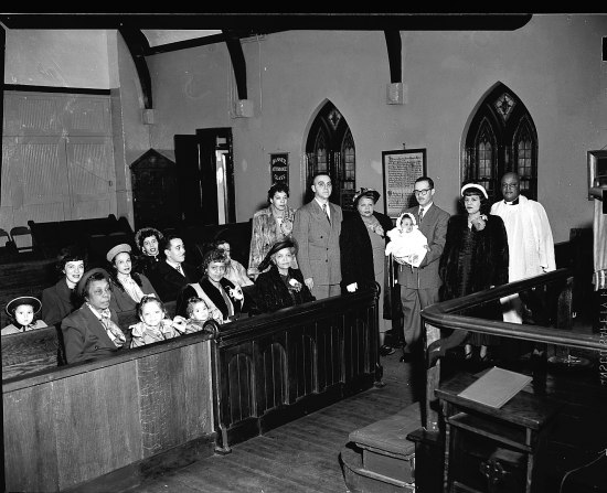 Photo from a church. About 10 people (adult women and children) sit in church pews, wearing hats. Nearby stands a group of people, parents, dad holding an infant, and a religious figure. Inside of church includes stained glass windows and little decoration. Folding chairs visible at back of room.