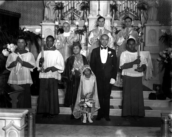 Eight adults and one young child at a church alter, with candles, plants, and Saint Michael statue in background. Religious leaders and altar servers stand with the child's mother or other female relative and the little girl, who wears a long veil, white shoes, white dress with fancy sleeves, and holds a bouquet. She isn't smiling.