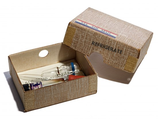 "An open brown box. The top of the box has a label reading ""via air mail"" and a stamp that says refrigerate, but no other markings. Insides the open box, there is a pipette and other components of the pregnancy test."