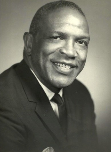 Black and white photo of an African American man. He wears a suit and has a friendly smile on his face. His hair is short.