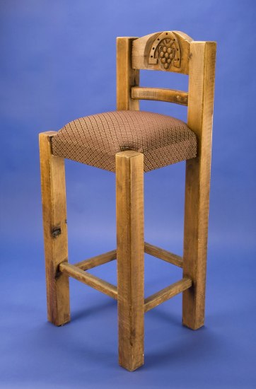 Tall wooden chair with a padded seat. On the back, a grapes are carved. The legs are also made of wood.