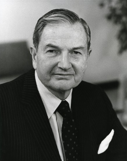Black and white portrait of man looking pleasantly at camera. He wears a suit and tie.