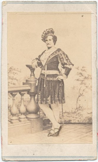 A faded photograph of a woman leaning against a balustrade. She is wearing a dark crown-like hat and a skirted outfit with embroidery.