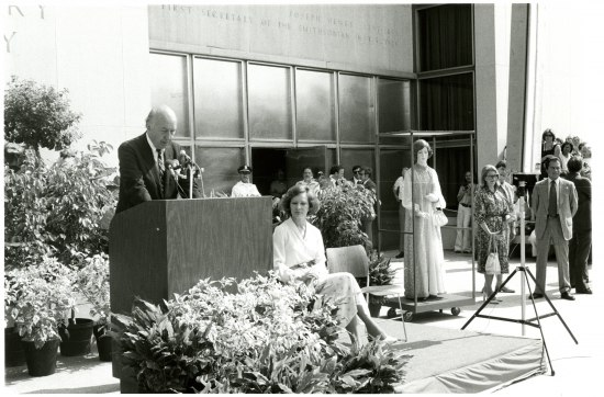 Outside the museum building, a man speaks at lectern. To his left, Rosalynn Carter sits in a chair wearing blouse and skirt. Beside her, a gown in a glass case on a mannequin.