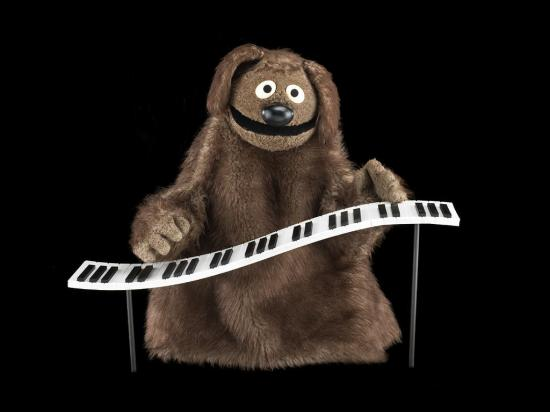 Brown furry puppet with smile and piano