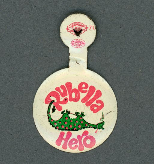 "Metal clip pin that could be worn on t-shirt. White background. Center image shows a dragon (green with red spots) laying on its back, defeated. Text ""Rubella Hero."""