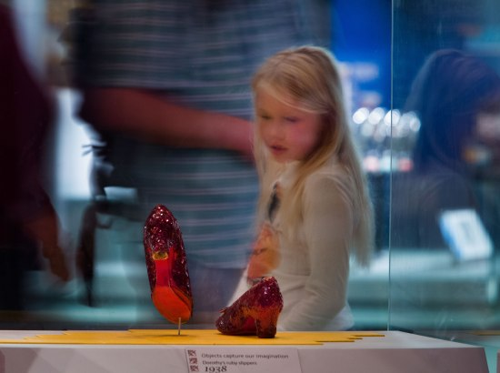 In foreground, pair of red shoes. In background, a little girl looks at them through plexiglass.