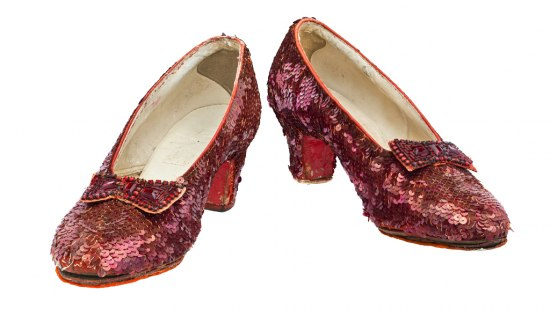 Photo of pair of shoes with a low heel. Covered in red sequins. Bow on each shoe has red beads.