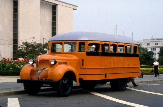 Photograph of orange school bus parked in front of the museum building.