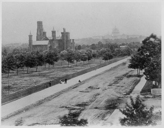 Photo form above of Smithsonian Castle, trees, long road with people who appear small due to distance