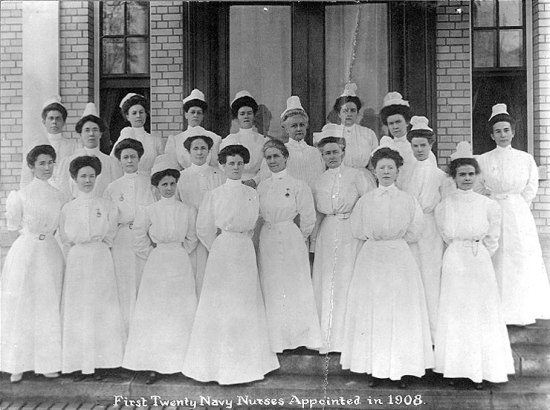 A black and white photographs of a group of women on the steps of a building. They are all wearing white dresses and hold their arms behind their backs. They wear a white fascinator-type object on their heads.