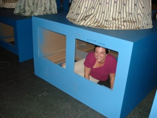 A woman sits in a large, long blue box with two squares cut out that look like windows. There is a dress on top of one of the boxes and on a similar box next to it there are hems of two more dresses.