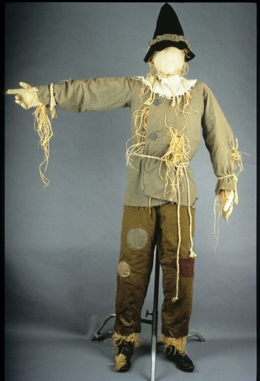 Photo of scarecrow costume with dark, pointed hat, burlap shirt and pants, all with hay poking out.