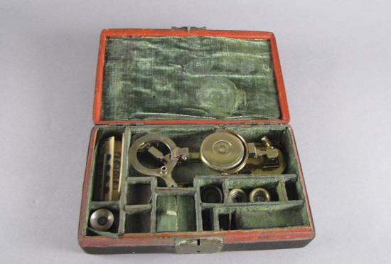 Wooden box lined with green velvet containing microscope parts