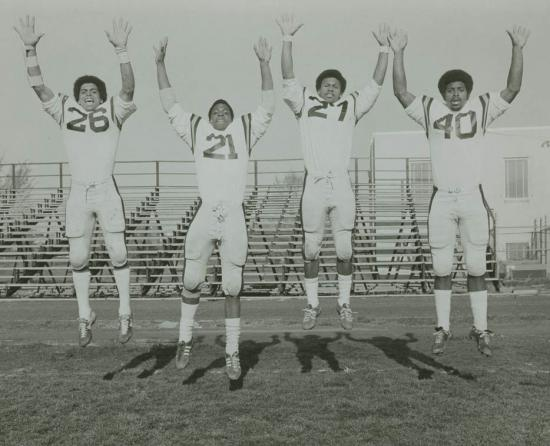 Four football players in uniforms jumping in air with arms raised. Bleachers in background.